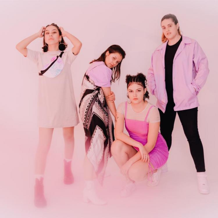 The 4 members of Pink Matter posing in front of a pink background