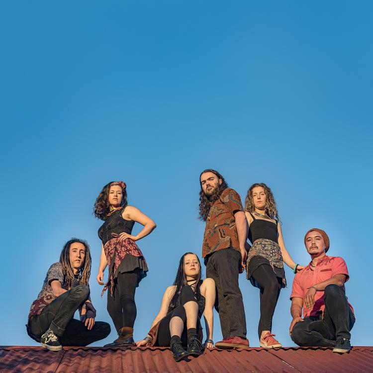 Rhythm Hunters posing on a roof with the blue sky behind them.  All members are at various levels