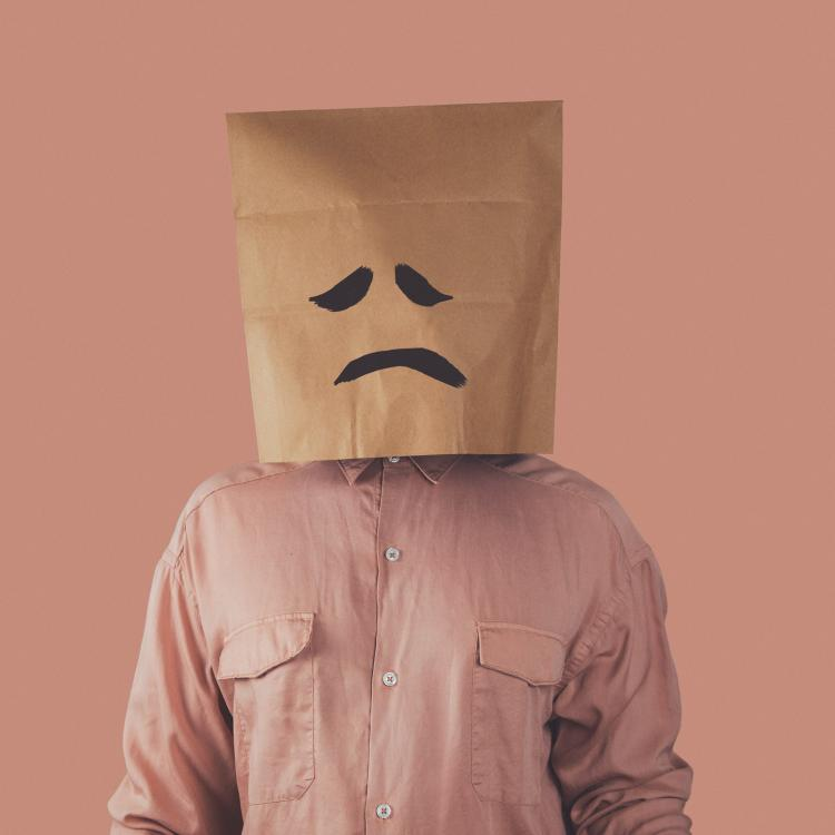 sad face. in a pink shirt with a sad paper bag on his head in front of a pink background
