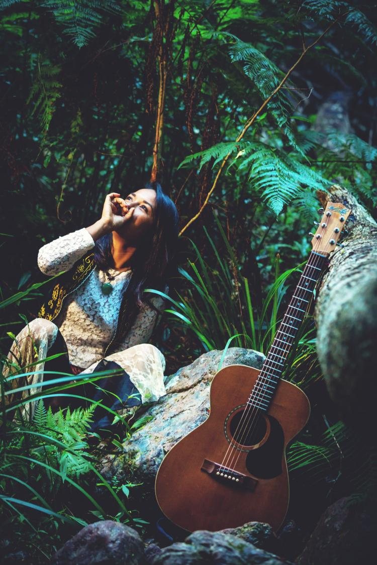Alisha Todd sitting in a forest holding her mouth with her guitar in the forefront of the photo.