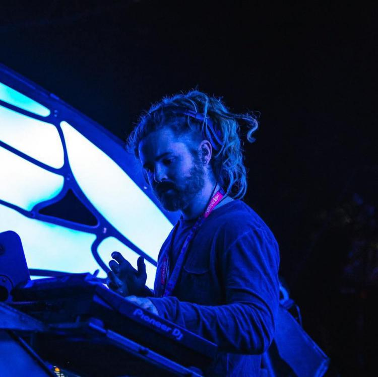 BustaFlux in a blue lit room DJing facing to the left of the frame.  He has dreadlocks and has a red lanyard around his neck.  There are lights behind him.