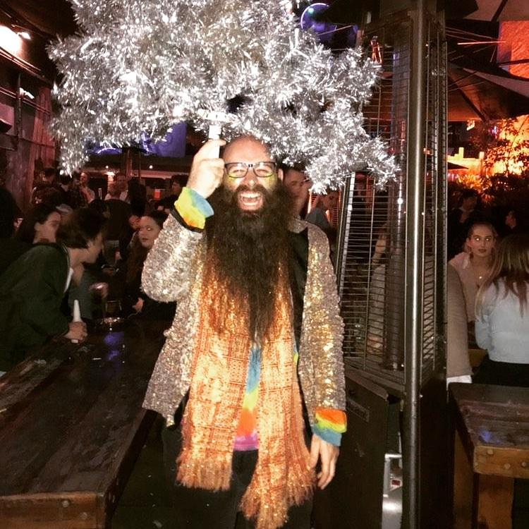 Man with beard holding Christmas tree above his head